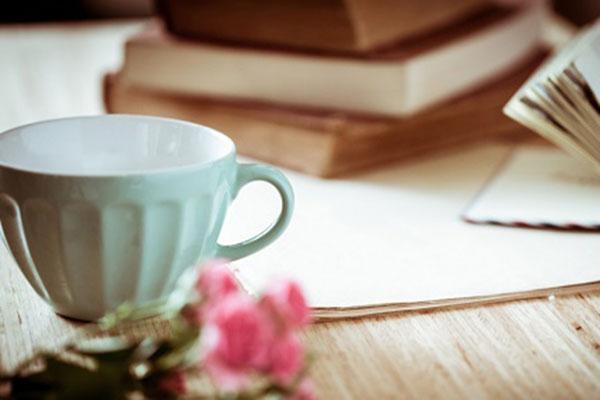 Kaffeetasse mit Blüte und im Hintergrund Bücher