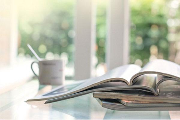aufgeschlagene Zeitschrift auf einem Zeitschriftenstapel auf einem Tisch